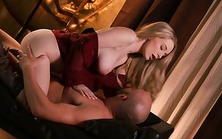 A blond is on her back in her devours clothes, staring at a dick